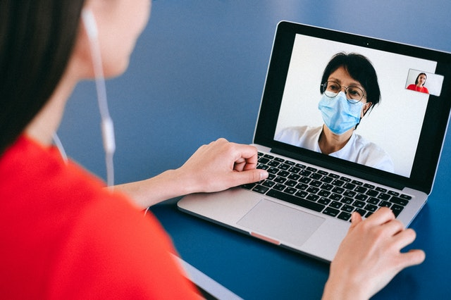 woman on video conference with covid-19 face covering